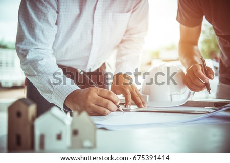 architect man and Engineer working with blueprints,engineer inspection in workplace for architectural plan,sketching a construction project ,selective focus.