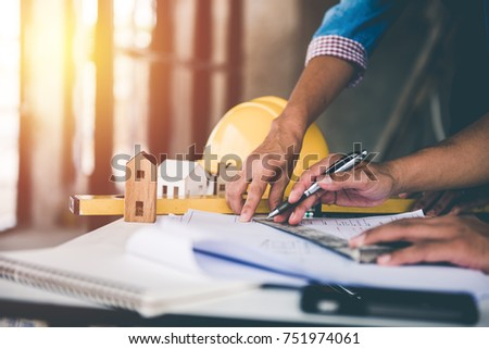 architect man working with blueprints,engineer inspection in workplace for architectural plan,sketching a construction project ,selective focus. #751974061