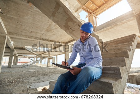 Architect or builder Siting on the stairs of the building site in his hardhat talking on a mobile phone as he reads a document in his hand. Young architect or inspector talking over his mobile phone