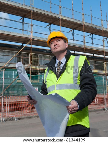 Architect or engineer at work on a building site. Checking plans against the construction work. Confident gaze.