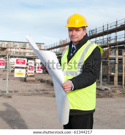 Architect or engineer at work on a building site. Checking plans against the construction work. Looking confidently at camera.