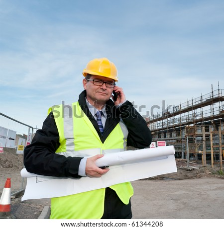Architect or engineer at work on a building site. Holding plans for construction work. Confident gaze and smile at camera. Using telephone.