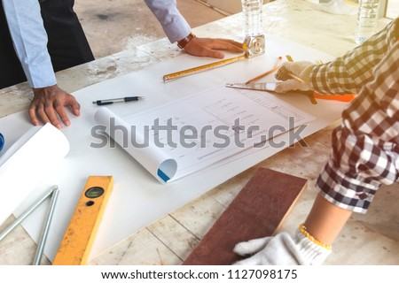 Architect or engineer discussion with construction blueprint at the table, Engineer inspection in workplace for architectural plan. Sketching a construction project. Business construction concept.