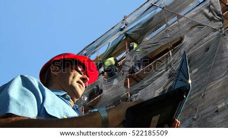 Architect or Engineer With Laptop Computer on a Building Site / Architect or Engineer typing on laptop computer and two workers on scaffolding in the background