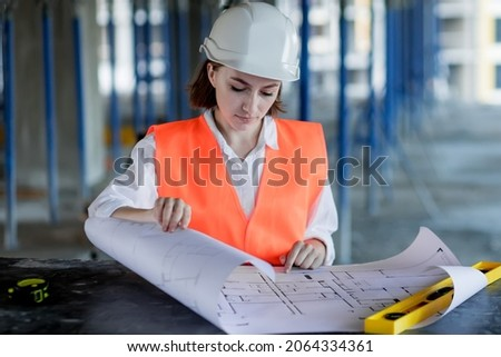 Architect or engineer working, browsing building project indoor of construction site with blueprint plan. Woman construction engineers or architects working people.
