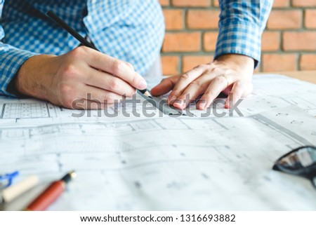 Architect or engineer working in office on blueprint. Architects workplace #1316693882