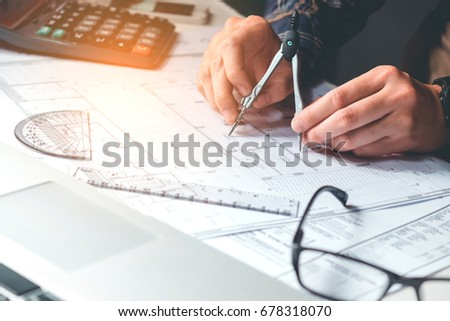 Architect or engineer working in office on blueprint. Architects workplace , blueprints, ruler, helmet and divider. Construction concept. Engineering tools #678318070