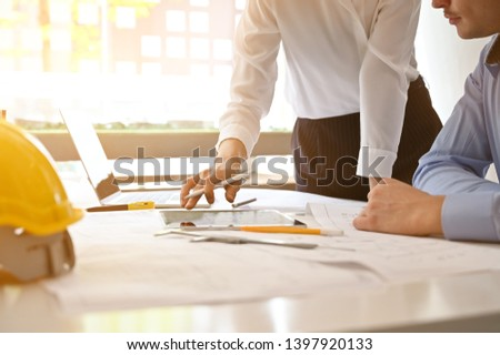 Architect planning blueprint in digital tablet with construction meeting and planning concept.