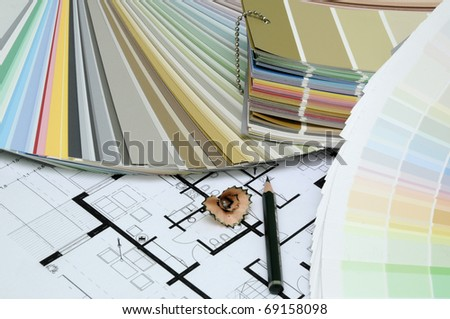 Architect's and Designer's desk during work. With technical drawing, color sample catalog and pencils.