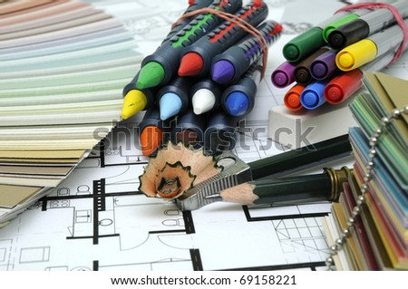 Architect's and Designer's desk during work. With technical drawing, color sample catalog, pencils, wax crayons and other tools.
