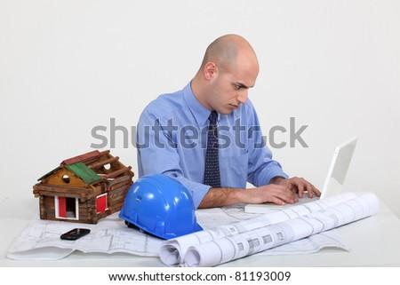 Architect sat at desk - stock photo