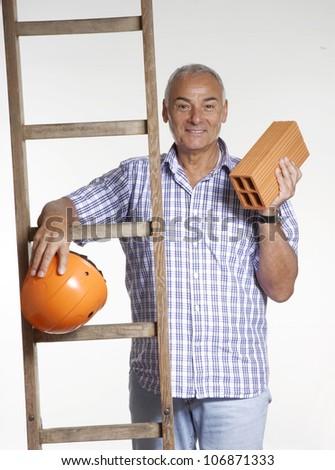 Architect senior man using helmet holding a brick behind a wood scale.
