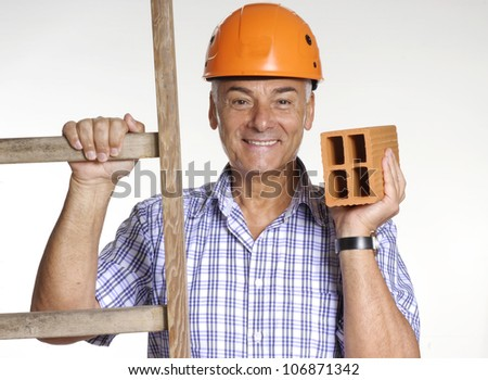 Architect senior man using helmet holding a brick behind a wood scale.