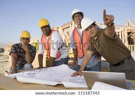 Architect showing blueprint to workers at construction site