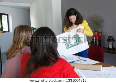 Architect showing house design to clients or colleagues. Women sitting back to camera at desk with drawings and office interior in background. House design concept. #1331004812