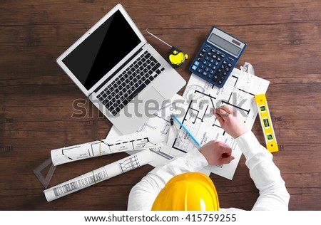 Architect sketching construction project on wooden table, top view