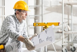 Architect, structural engineer or builder kneeling on the floor in a building under construction holding a blueprint or plans