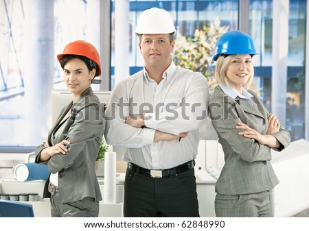 Architect team wearing hardhat in office, posing for portrait, looking at camera, smiling.?