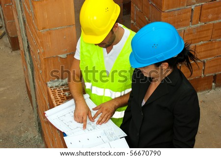 Architect team with projects having a conversation and  the man pointing on plan and showing something to his colleague woman