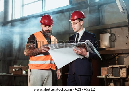 Architect The Suit And Helmet And Foreman Builder In Overalls And With A  Tattoo Compare Their