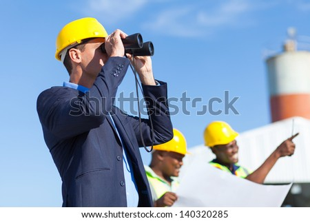 architect using binoculars looking at construction site with construction workers #140320285