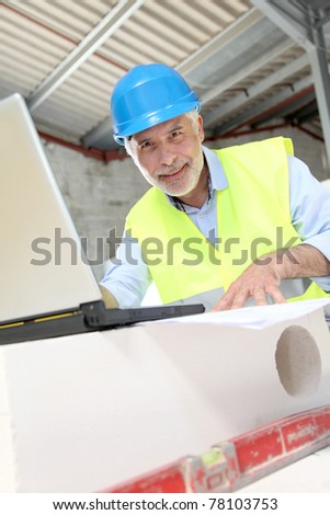 Architect using laptop computer on construction site
