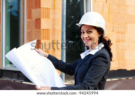 architect with blueprint before shell of a house building a house.