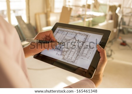 Architect woman working with stylus on electronic tablet