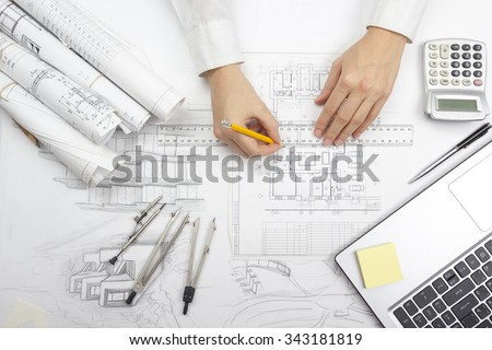 Shutterstock Architect working on blueprint. Architects workplace - architectural project, blueprints, ruler, calculator, laptop and divider compass. Construction concept. Engineering tools. Top view