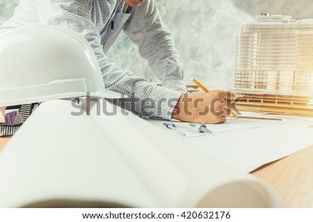 Architect working on blueprint. Architects workplace - architectural project, blueprints, ruler, helmet and divider. Construction concept. Engineering tools #420632176