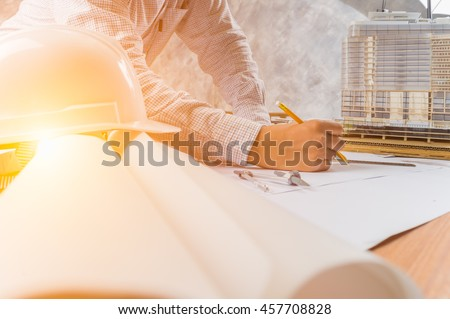 Architect working on blueprint. Architects workplace - architectural project, blueprints, ruler, helmet and divider. Construction concept. Engineering tools