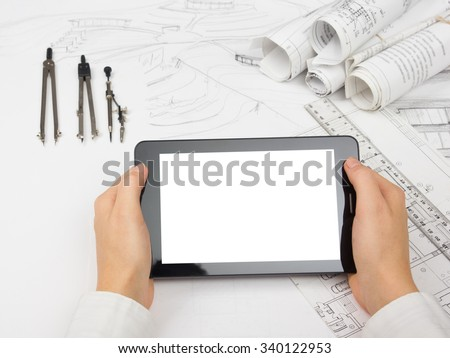 Architect working on blueprint. Architects workplace - architectural project, blueprints, tablet pc, divider compass. Construction concept. Engineering tools. Copy space for text.