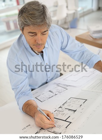 Architect working on blueprint in office