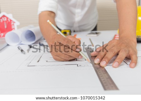 Architect working on blueprint with architect equipments on desk at workplace. #1070015342