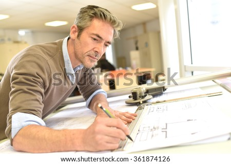 Architect working on drawing table in office #361874126