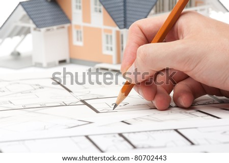 Architect working with blueprints and model of the family house