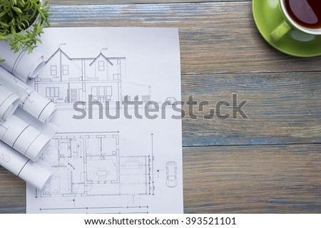 Architect worplace top view. Architectural project, blueprints, blueprint rolls and  divider compass, calipers on vintage wooden desk table. Construction background. Engineering tools. Copy space