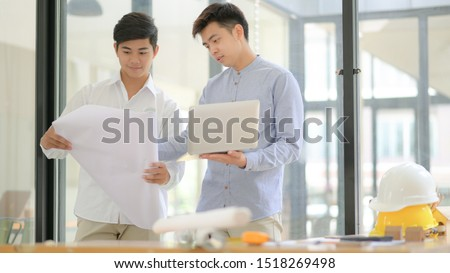 Architects and engineers inspect floor plans and use laptops to design and plan construction work. #1518269498