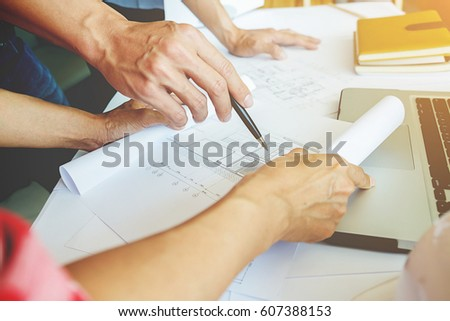 Architects engineer discussing at the table with blueprint - Closeup on hands and project print. #607388153