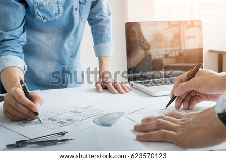 Architects engineer discussing at the table with blueprint - Closeup on hands and project print, Team group on construciton site check documents and business workflow. #623570123