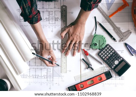 Architects is designing blueprints for home construction. #1102968839