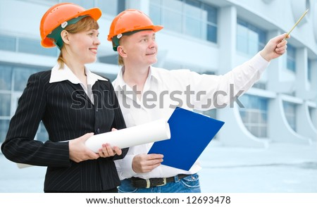 architects man and woman  protective helmet standing in front of a building