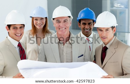 Architects with hardhats in a building site smiling at the camera