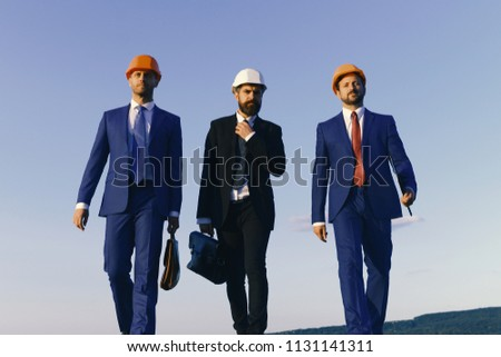 Architects with strict faces in suits, white and orange helmets. Builders walk confidently and adjust tie on blue sky background. Business and building concept. Engineers hold black and brown cases #1131141311