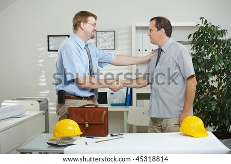 Architects working at office - shaking hands, smiling.