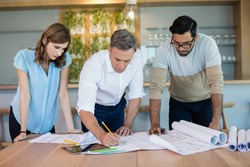 Architects working over blueprint in conference room at office