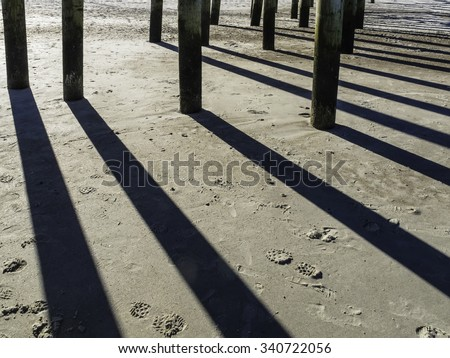 Architectural abstract for coastal explorers: Long afternoon shadows of wooden pilings that support a long pier above sandy beach at low tide along the Atlantic coast of Florida