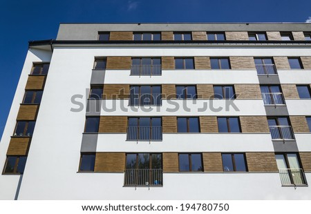 Architectural background of a modern stylish  apartment building, white facade decorated with wood against blue sky