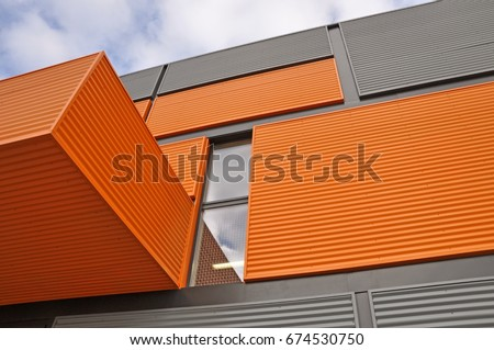 Architectural background. Wall of the modern orange and black corrugated metal panels. Look up. #674530750