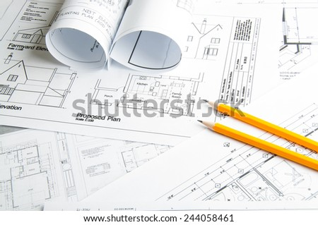 Architectural blueprints and blueprint rolls and two yellow pencils #244058461